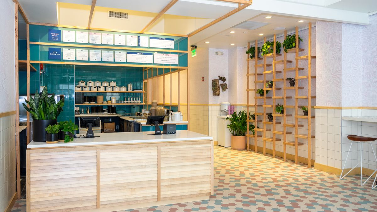 The inside of Little Sesame, with pale wooden accents and plenty of green plants on the wall