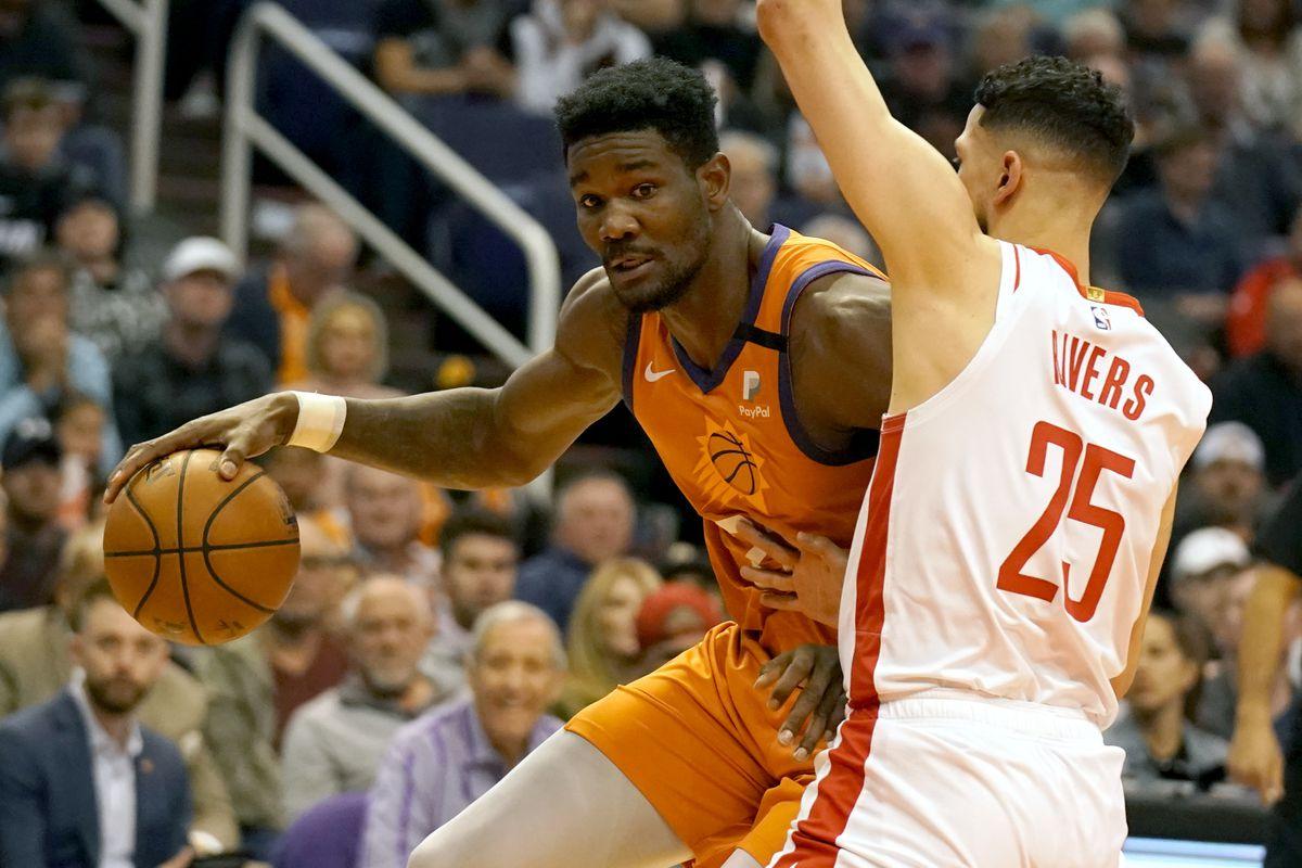 Phoenix Suns center Deandre Ayton drives on Houston Rockets guard Austin Rivers at Talking Stick Resort Arena.