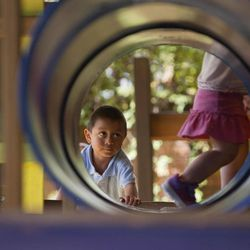 In this Friday, Sept. 7, 2012 photo,  Ellyson Hooker, right, runs ahead of her adopted brother Daniel as they play together at a restaurant in Guatemala City. Daniel was 18 months old when the Tennessee couple Ryan and Jessica Hooker began the process to adopt him in Guatemala. They just got him at age 6. His is one of hundreds of adoption cases that were put in limbo five years ago, when the Guatemalan government declared a moratorium on international adoptions because of irregularities and fraud.