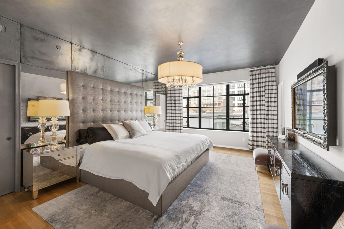 A bedroom with a large bed, hardwood floors, large windows, and a mirror on top of each nightstand.