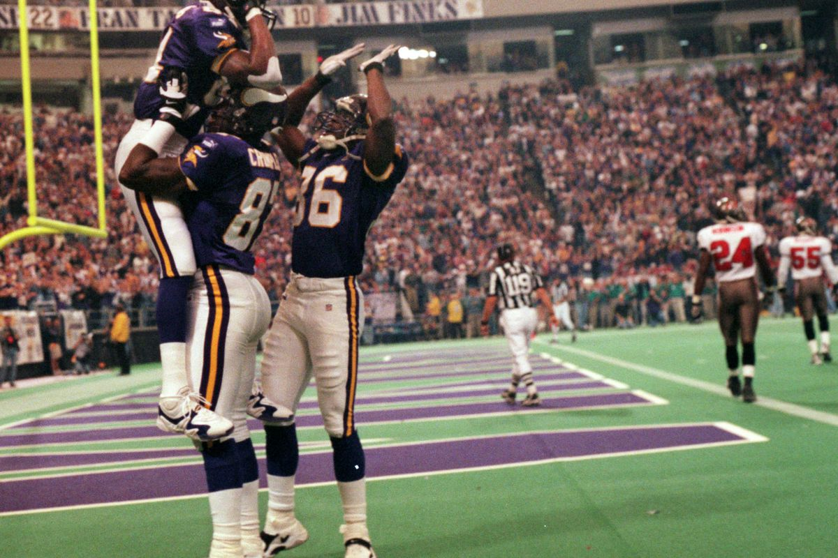 Minneapolis, MN 10/3/99 Vikings vs. Tampa Bay Buccaneers — Randy Moss is congratulated by receiver Jake reed, right, as he is lifted in the air by tight end Carlester Crumpler after Moss scored his first touchdown of the fgame, early in the first quarter