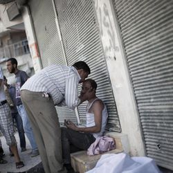 A Syrian man is comforted after the death of his brother, killed by a Syrian Army sniper, outside Dar El Shifa Hospital in Aleppo, Syria, Thursday, Sept. 27, 2012.