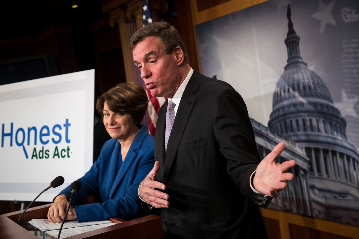 Sen. Amy Klobuchar (D-MN) looks on as Sen. Mark Warner(D-VA)stands at a podium to announce legislation to prevent foreign interference in elections