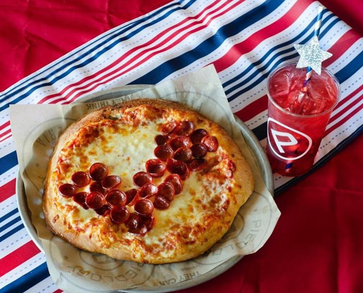 A pizza and a drink on a red, white, and blue piece of fabric