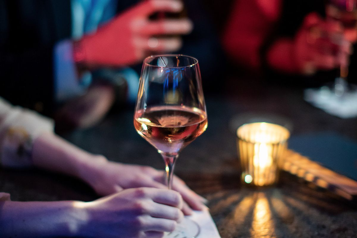 A woman's hand holds the stem of a glass of wine on a table in a dark bar.