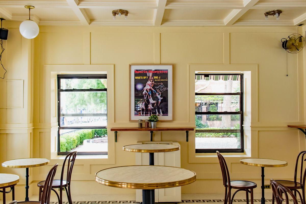 A photograph of an indoor dining room, with a poster of a Sports Illustrated cover at one end of the room