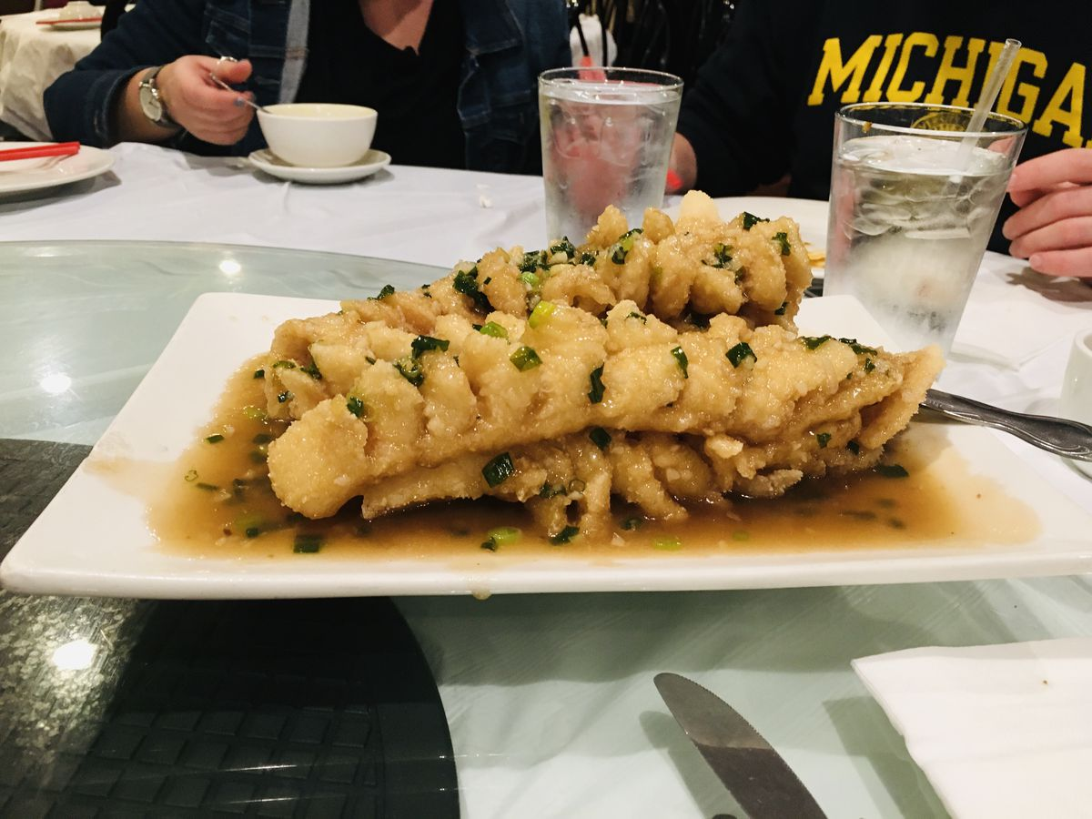 Squirrel-shaped fried fish in brown sauce on a rectangular plate.