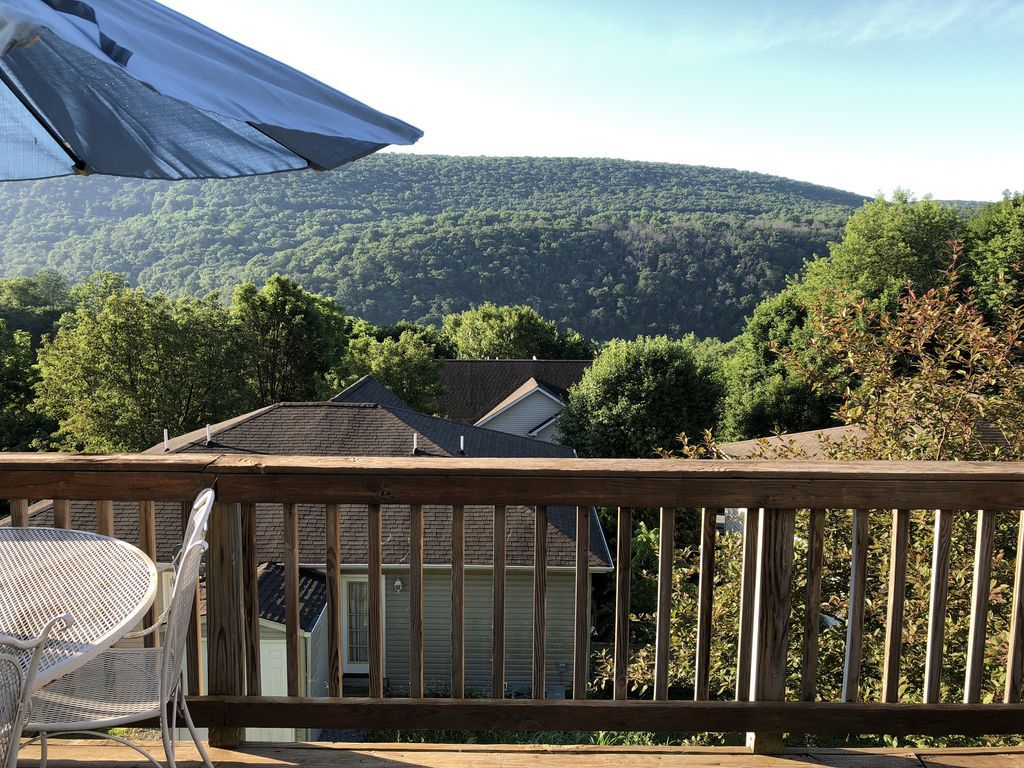 The view from the deck of a townhome in Harpers Ferry, West Virginia, showing hills and trees in the background.