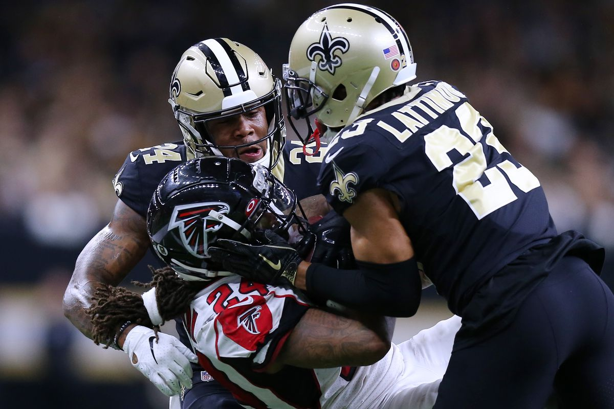 Devonta Freeman of the Atlanta Falcons is tackled by Marshon Lattimore of the New Orleans Saints and Vonn Bell during the first half of a game at the Mercedes Benz Superdome on November 10, 2019 in New Orleans, Louisiana.