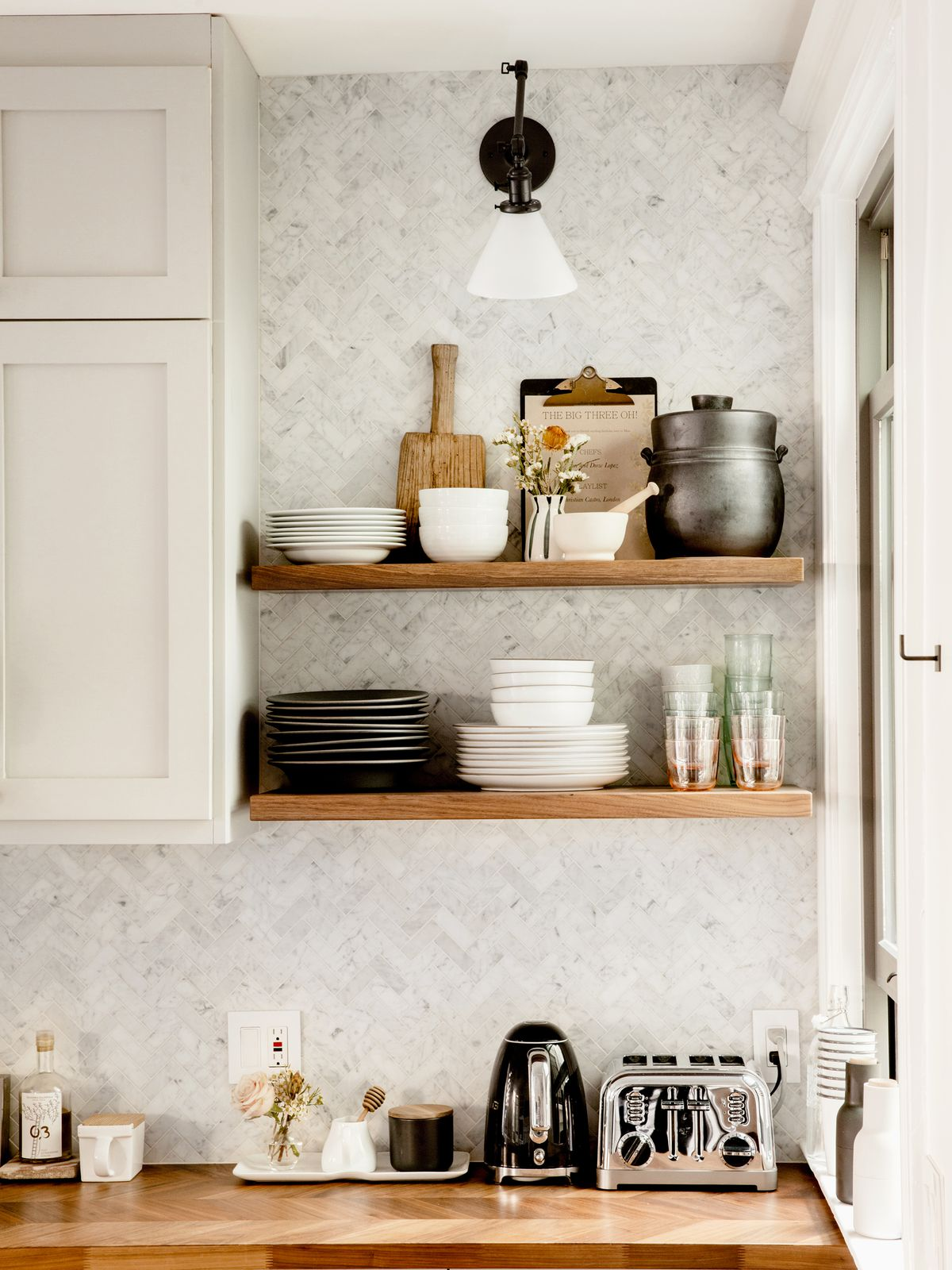 Wooden shelves above a kitchen countertop hold various kitchen objects and appliances. There is a toaster, kettle, and other kitchen objects on the countertop. The wall is decorated in grey and white patterned wallpaper. The cabinetry is white.