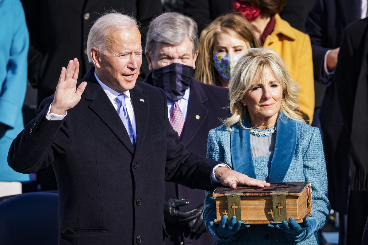 Biden gives the oath of office with his hand on a Bible held by Jill Biden.