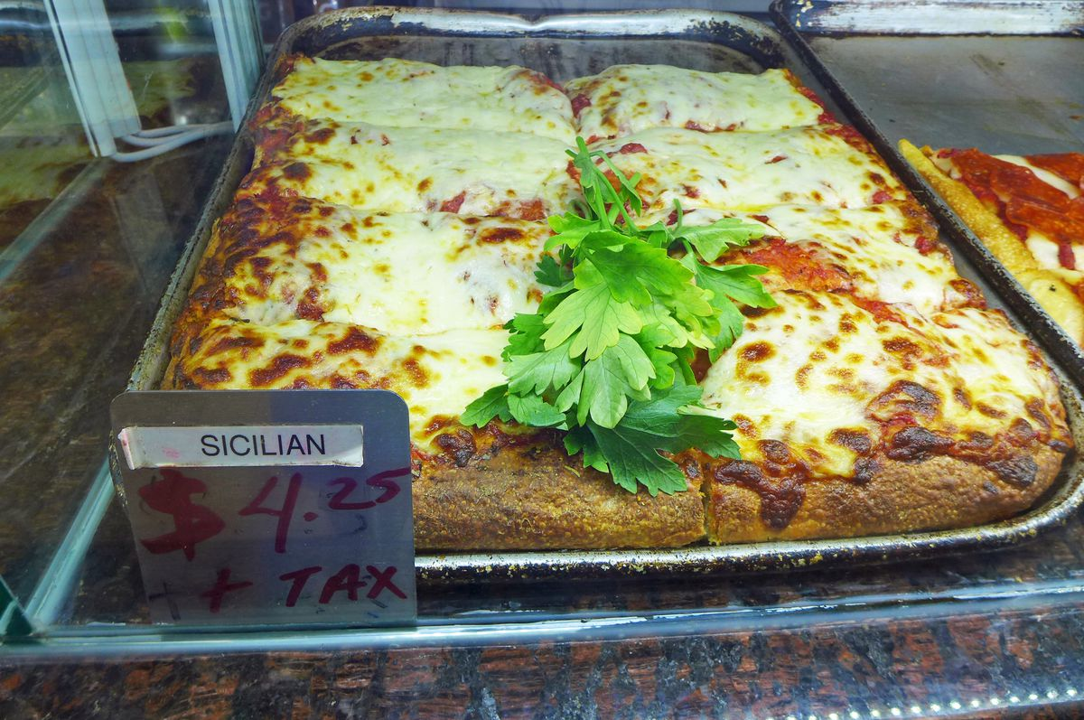 A tray of square slices with lots of browned cheese on top.