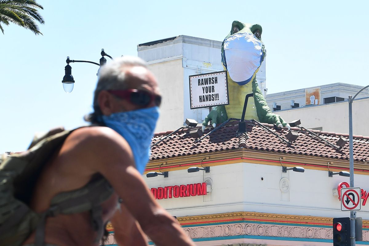"""A cyclist wearing a bandana over his moth and nose rides past the face-mask-wearing dinosaur atop the """"Ripley's Believe It Or Not"""" Museum displaying a sign that reads """"Rawrsh Your Hands"""" on April 23 in Hollywood, California."""
