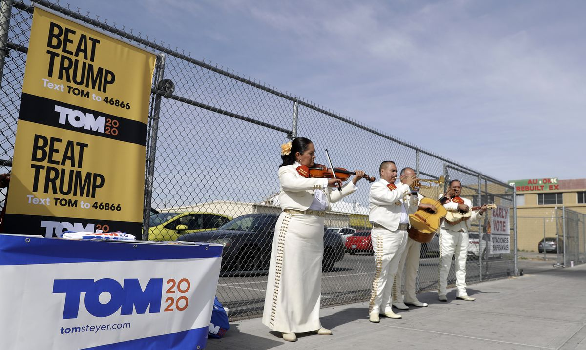 A mariachi band in gold and white plays besides Tom Steyer campaign signage.