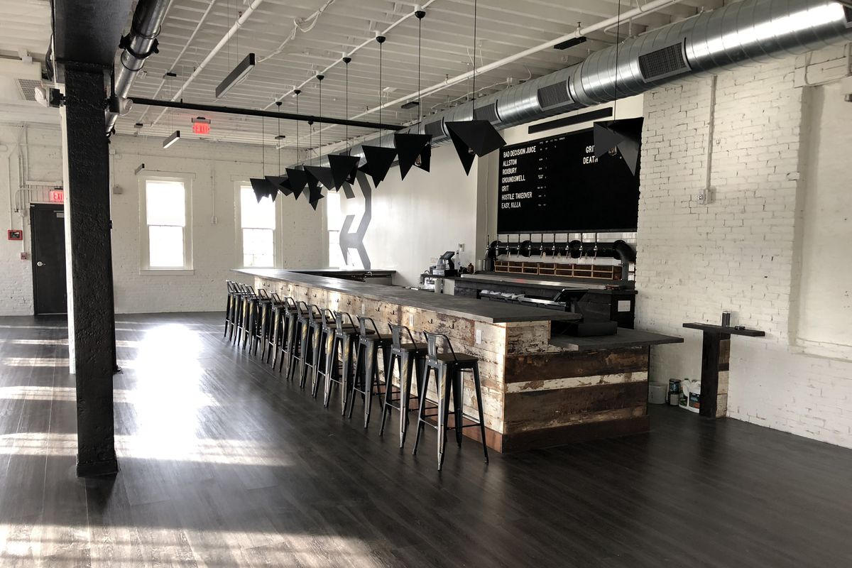 A spacious taproom built out in a former mill space, with white walls, one load-bearing beam, and a sparse, modern bar.