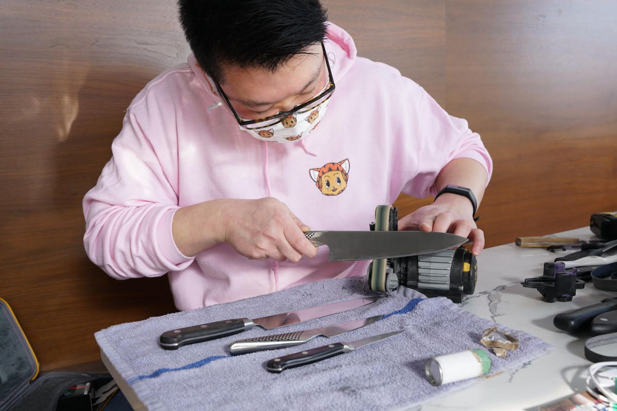 James Lim sharpens a knife wearing a pink hoodie and a mask