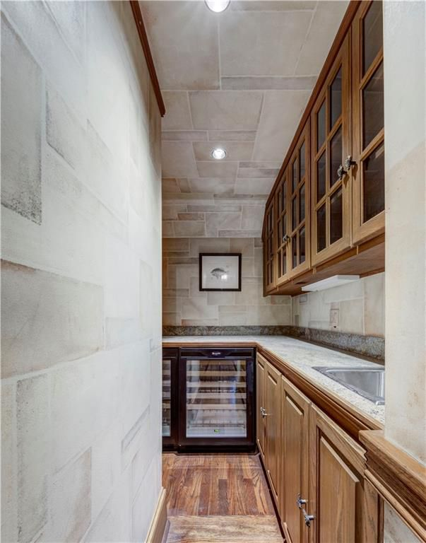 A long low kitchen space with a wine fridge.