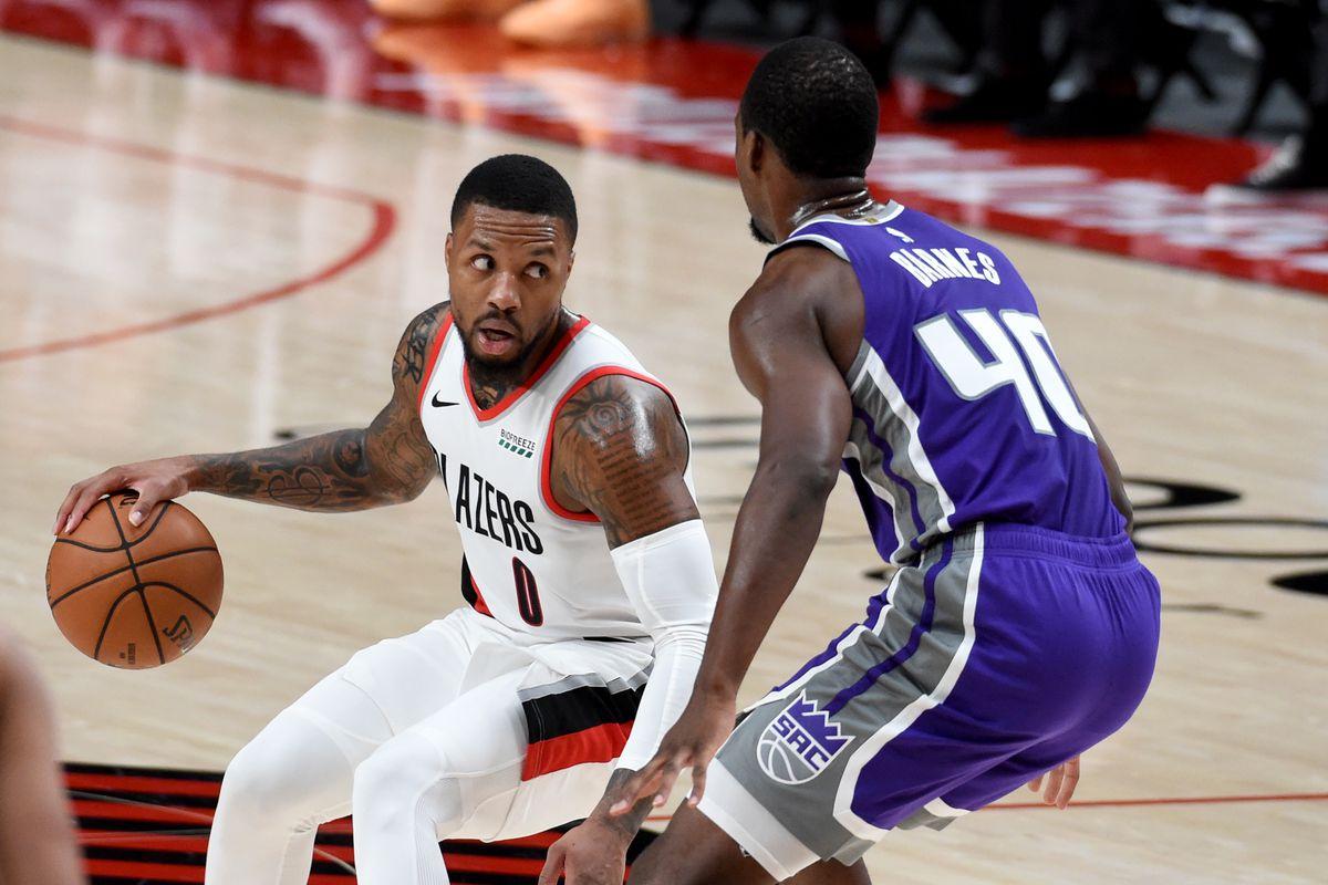Portland Trail Blazers guard Damian Lillard drives to the basket on Sacramento Kings forward Harrison Barnes during the second half of the game at Moda Center. The Blazers won 127-102.