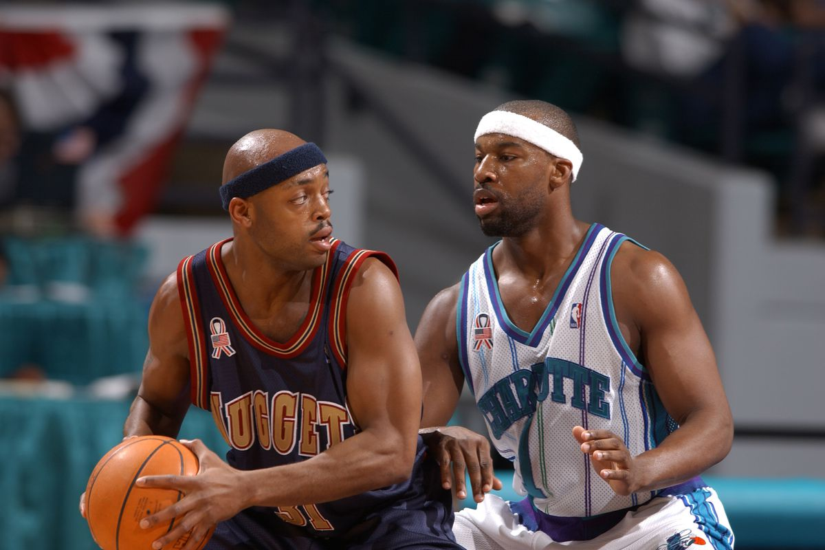 Baron Davis #1 of the Charlotte Hornets tries to contain Nick Van Exel #31 of the Denver Nuggets in Charlotte, North Carolina.