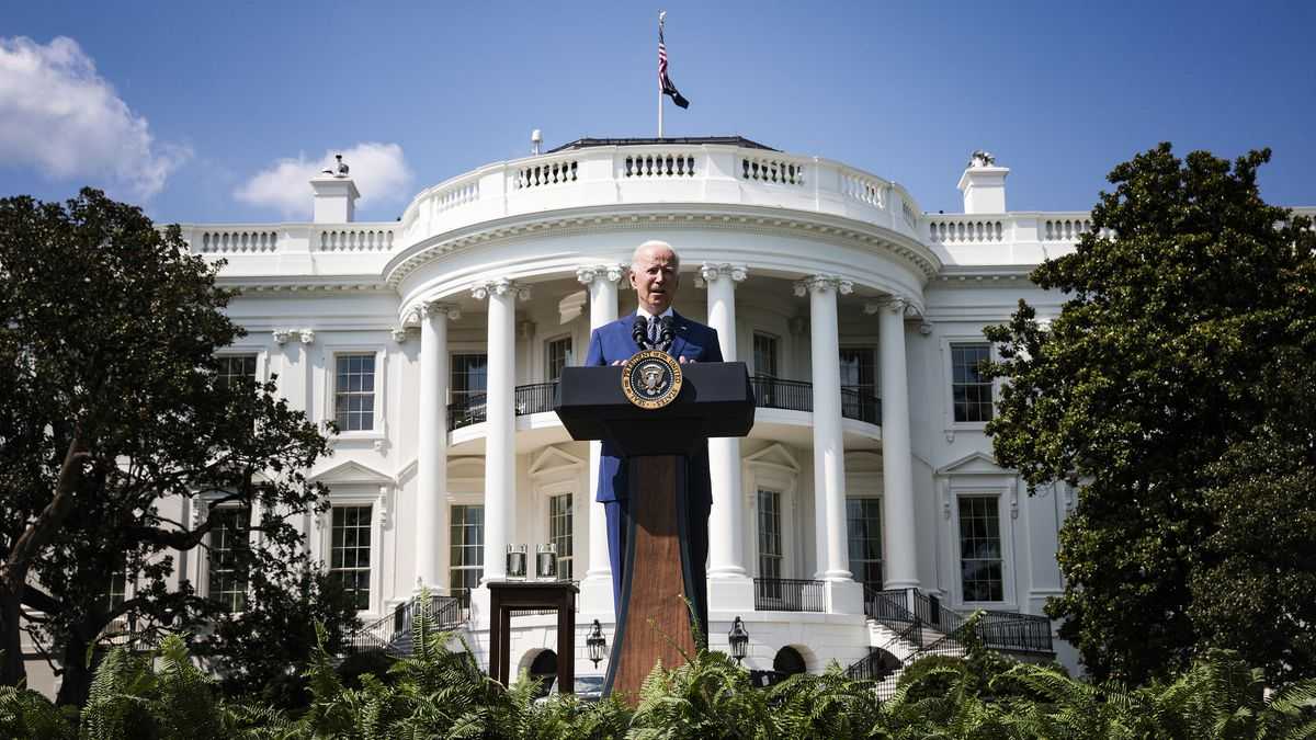 President Biden speaks from an outdoor lectern with the White House behind him.