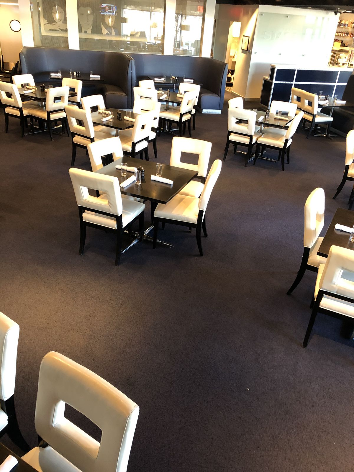 The dining room at stage deli has gray booths and white chairs. Everything is spread out due to reduced capacity.