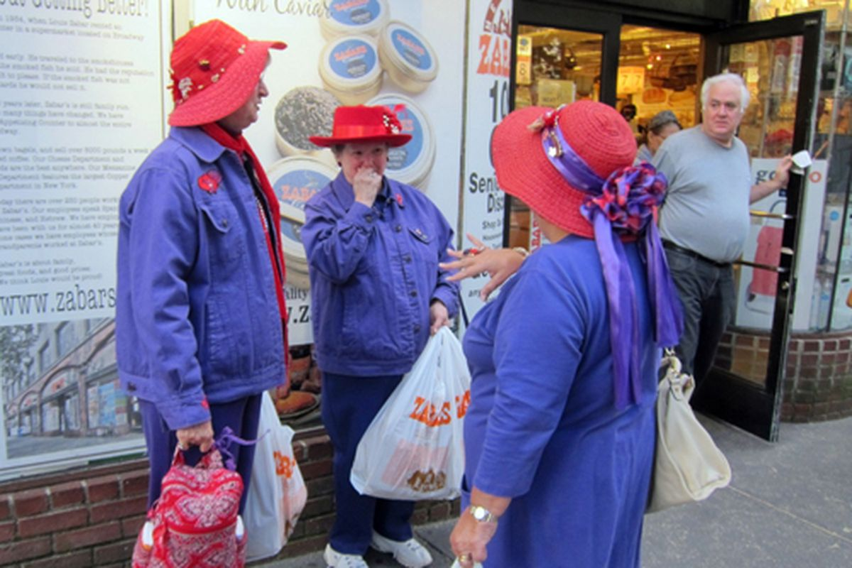 """The Purple Coat Red Hat Club convenes outside Zabar's. Via <a href=""""http://www.flickr.com/photos/62159569@N08/6171395318/in/pool-312691@N20/"""">Scoboco</a>/Racked Flickr Pool."""