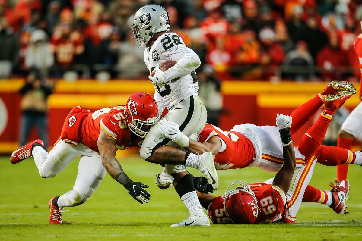 Damien Wilson of the Kansas City Chiefs and Anthony Hitchens of the Kansas City Chiefs combine on a tackle of Josh Jacobs of the Oakland Raiders during the second quarter at Arrowhead Stadium on December 1, 2019 in Kansas City, Missouri.