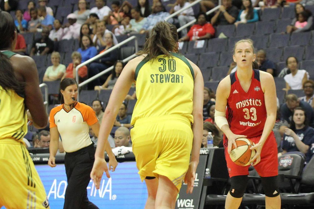 Emma Meesseman of the Washington Mystics is about to shoot a three point shot while Crystal Langhorne and Breanna Stewart of the Seattle Storm are surprised she is open.