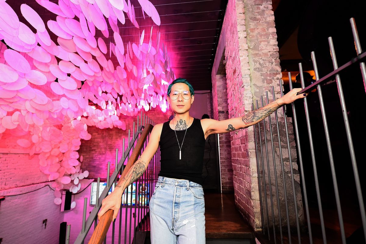Danny Bowien stands on a stairwell with a pink background