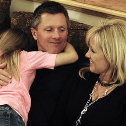U. coach Kyle Whittingham relaxes with daughter Kylie and wife Jamie at their home in Sandy.