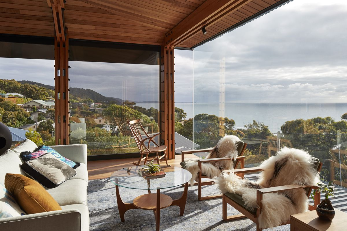 Shot from inside corner of house with full expanse of windows overlooking beach and a hill of houses below. Furniture is minimalist and Scandinavian-esque.