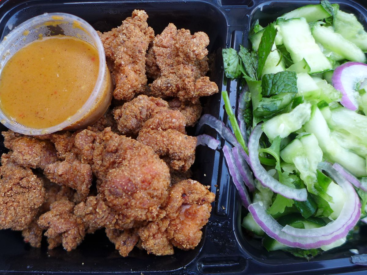 A heap of breaded chicken nuggets with brownish red dipping sauce and raw vegetables on the side.