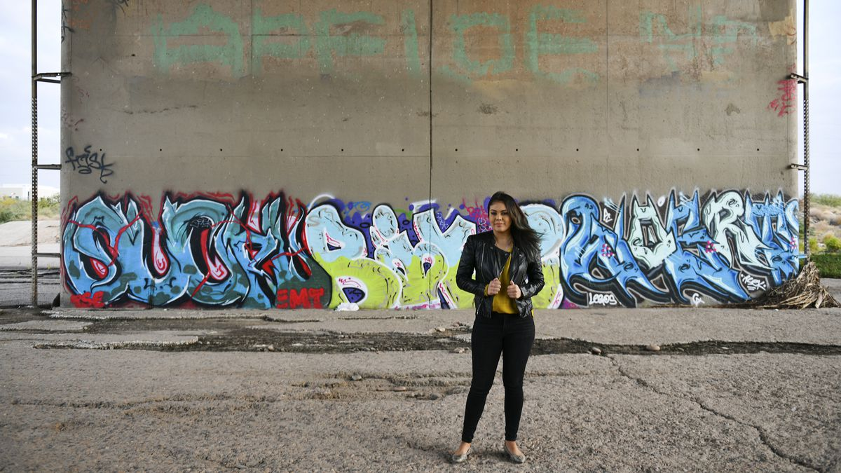 A young woman standing in front of a graffitied wall.