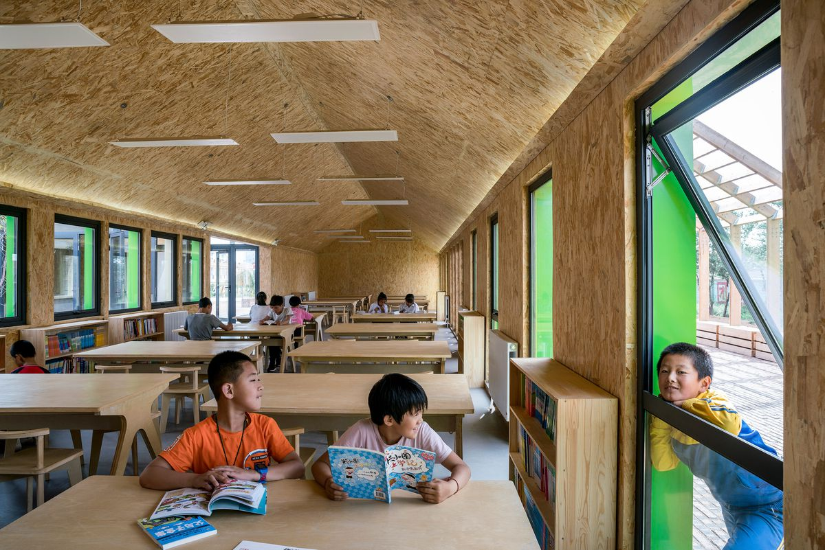Children sitting at desks inside library