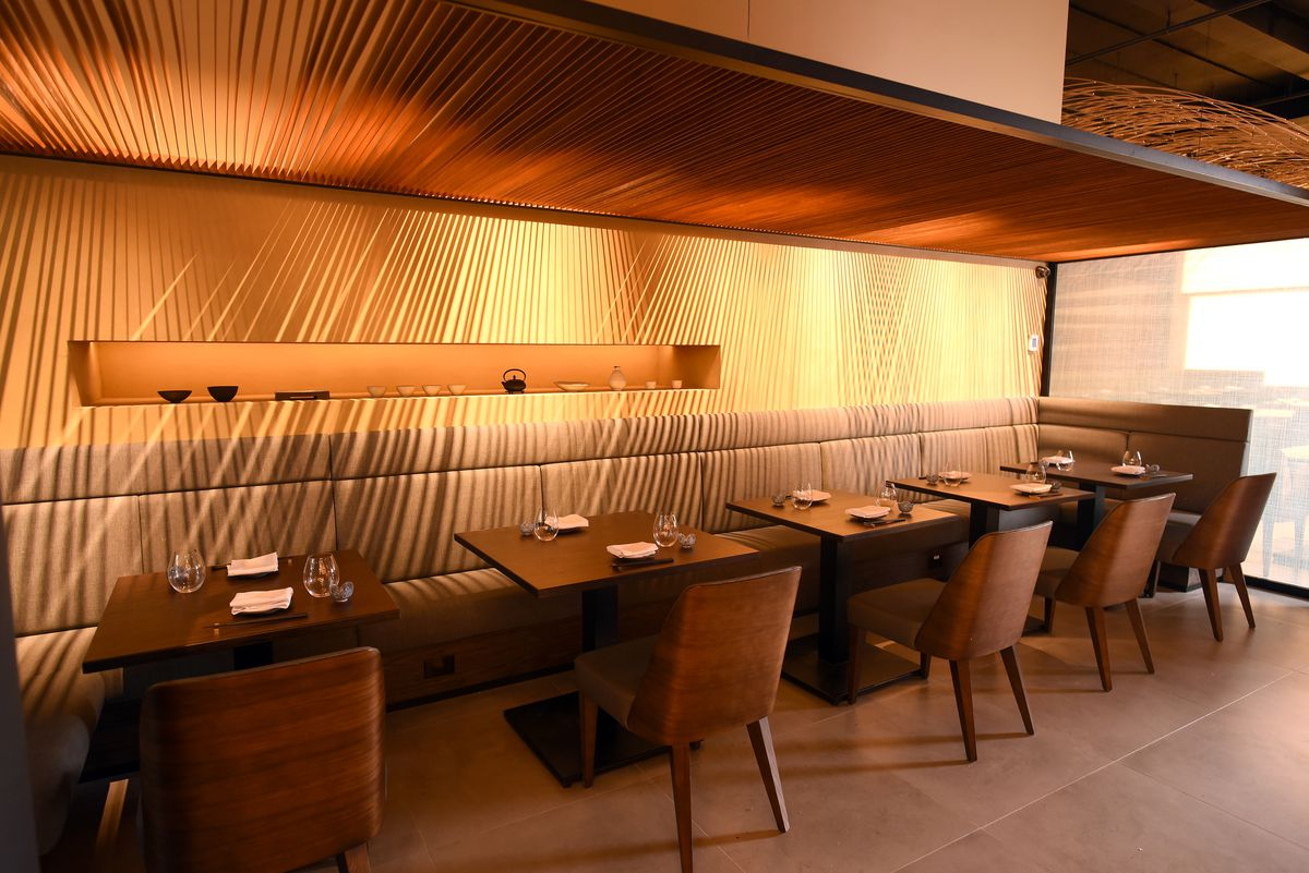 An intimate indoor dining room, half of which is made up by booth seating and dark wooden tables and chairs