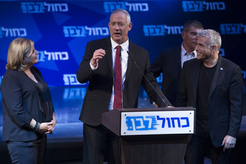 Israel's Blue and White leader Benny Gantz standing at a podium and speaking to an audience.