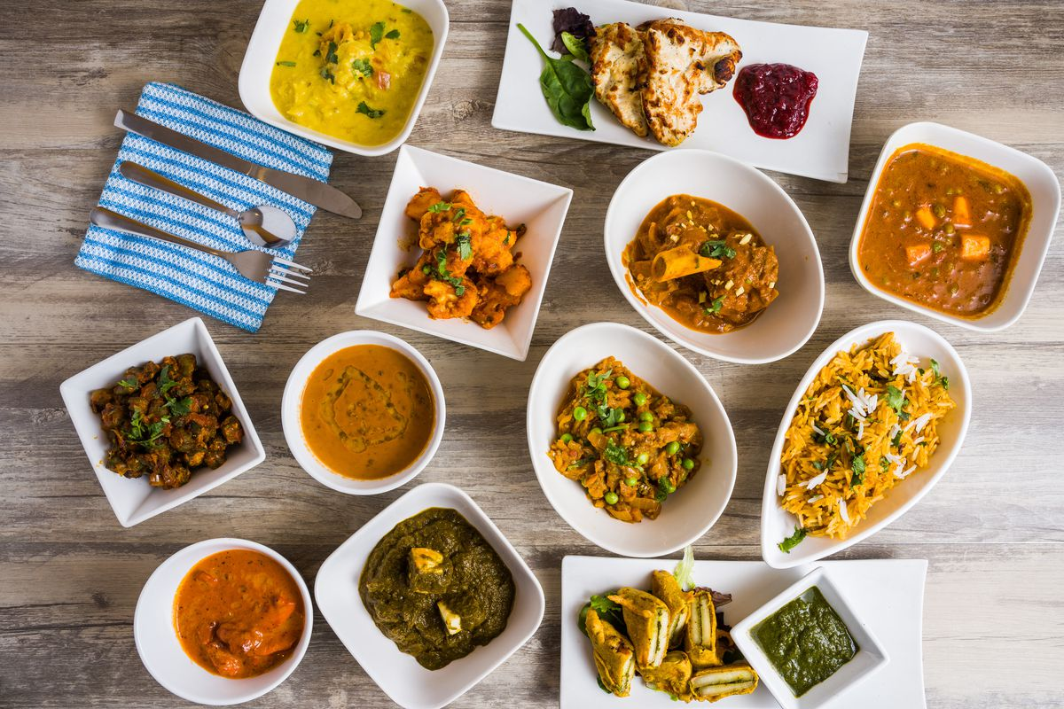 White serving platters and bowls with a variety of Indian foods, including curries, breads, and rice, are spread out on a gray wooden table