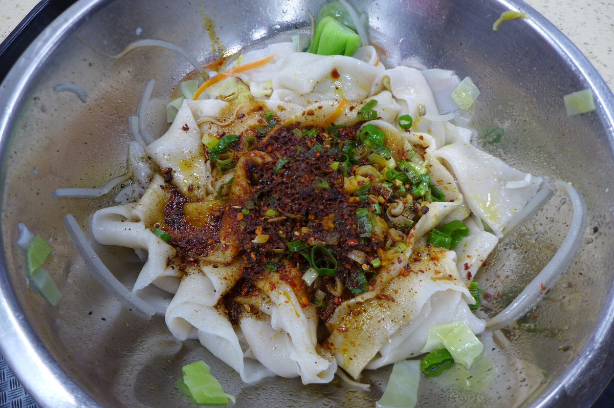 A metal bowl with white noodles and an array of spices and diced green vegetables layered on top