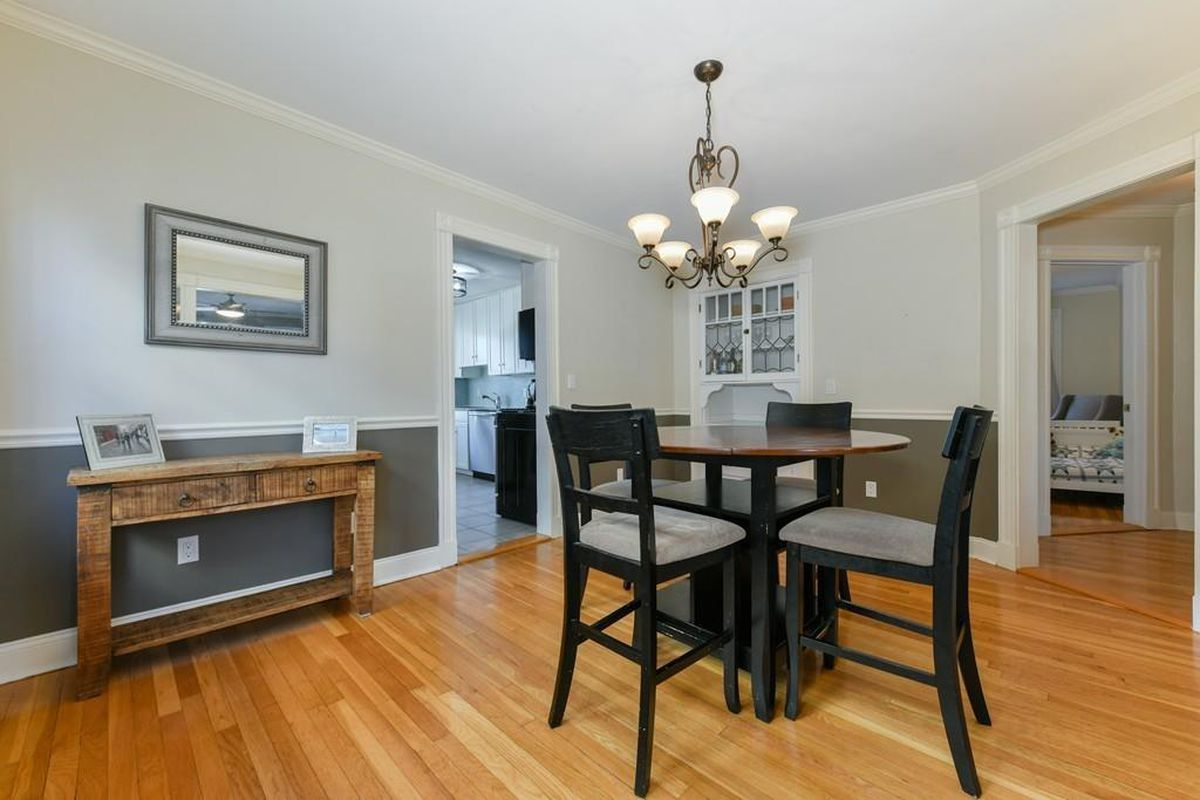 A sleek, well-proportioned dining room with a table and chairs, and there's a doorway leading to a kitchen.