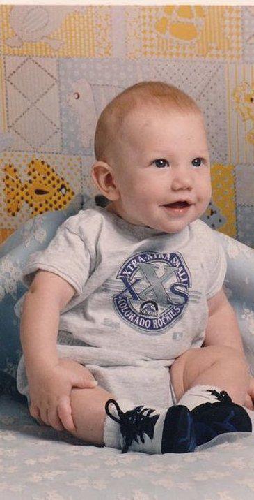 A baby wearing a Colorado Rockies onesie