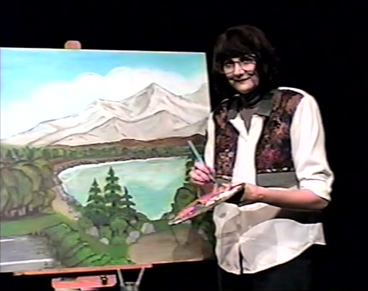 Kerri Kenney stands in front of an easel.