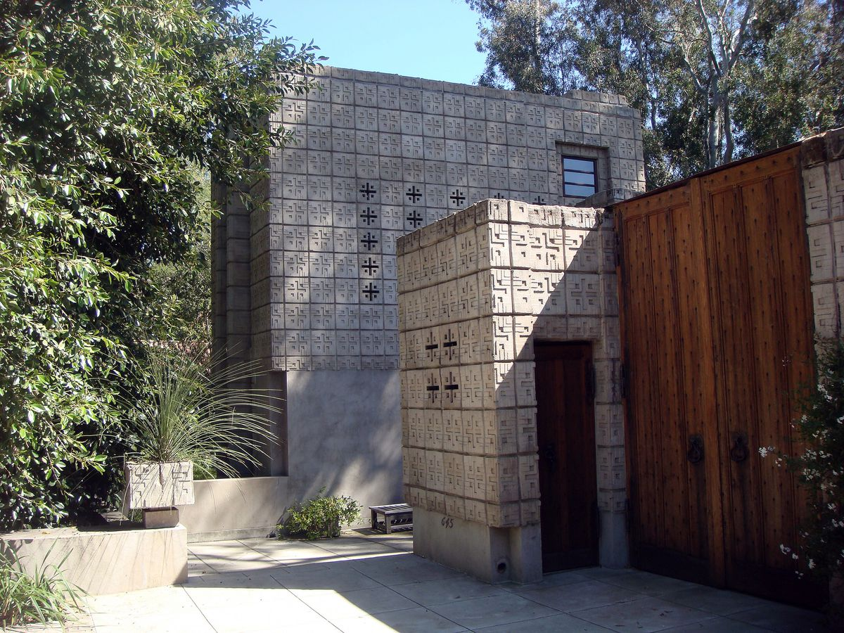Millard House by Frank Lloyd Wright. The facade is decorative concrete blocks. The doors are wooden.