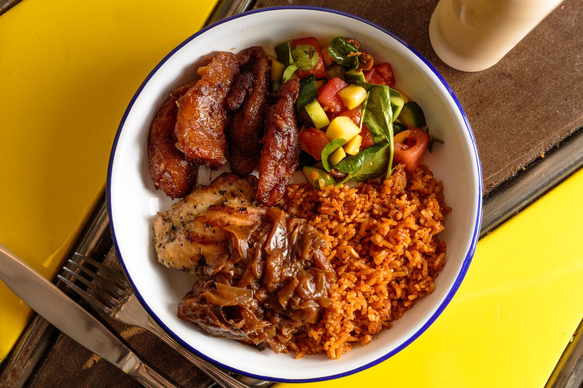 Chicken yassa sits in a white bowl alongside sweet plantains and tomato rice at Teranga