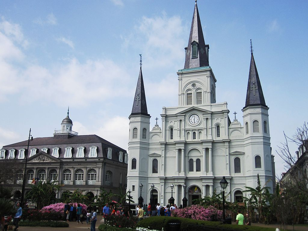 The exterior of the St. Louis Cathedral in New Orleans. The facade is light grey with a dark grey roof and towers.