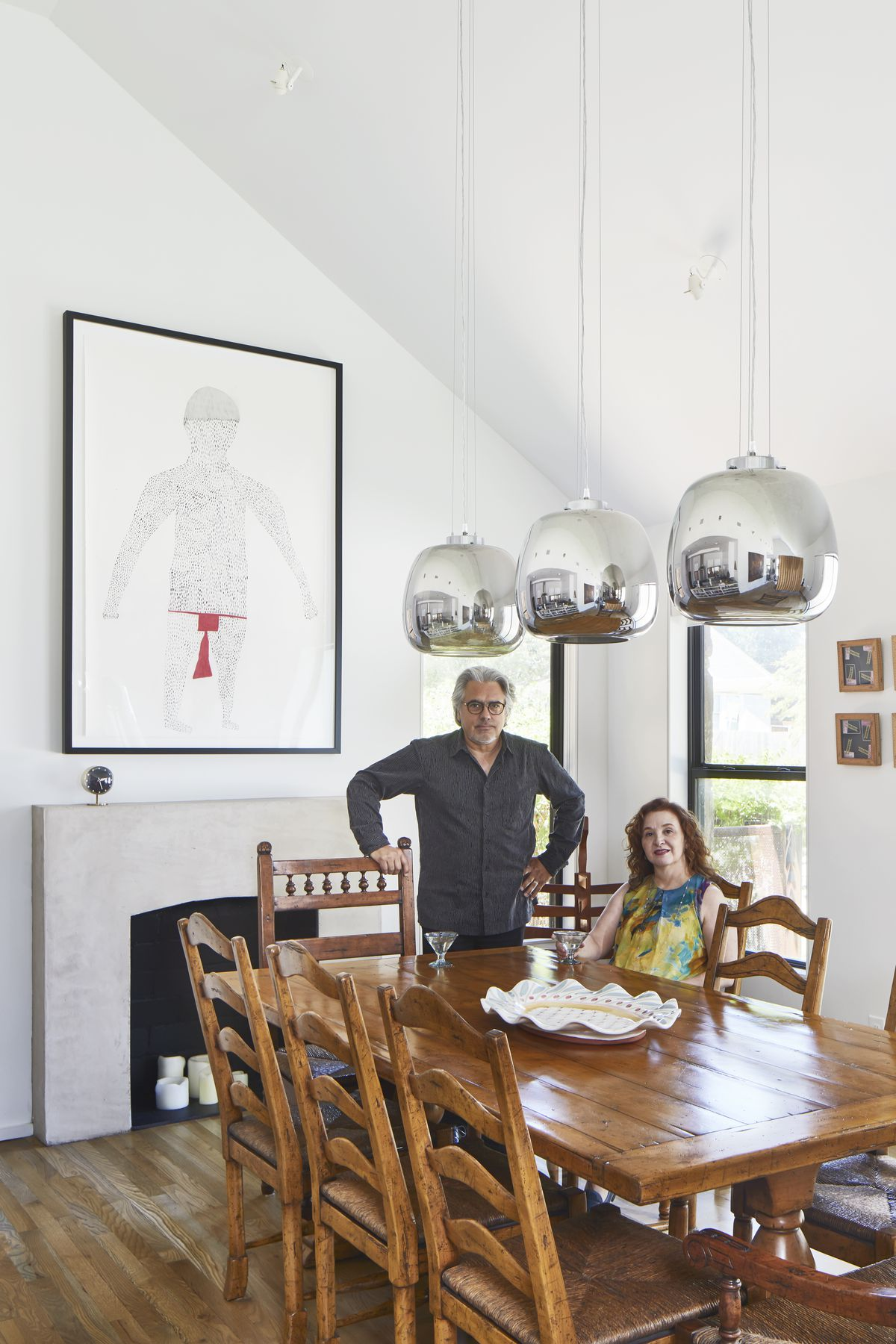 The homeowners, a man and a woman, are in the dining area of their home. The woman is sitting at a large wooden table and then man is standing next to her. They are both looking at the camera. There are multiple light fixtures above the table.