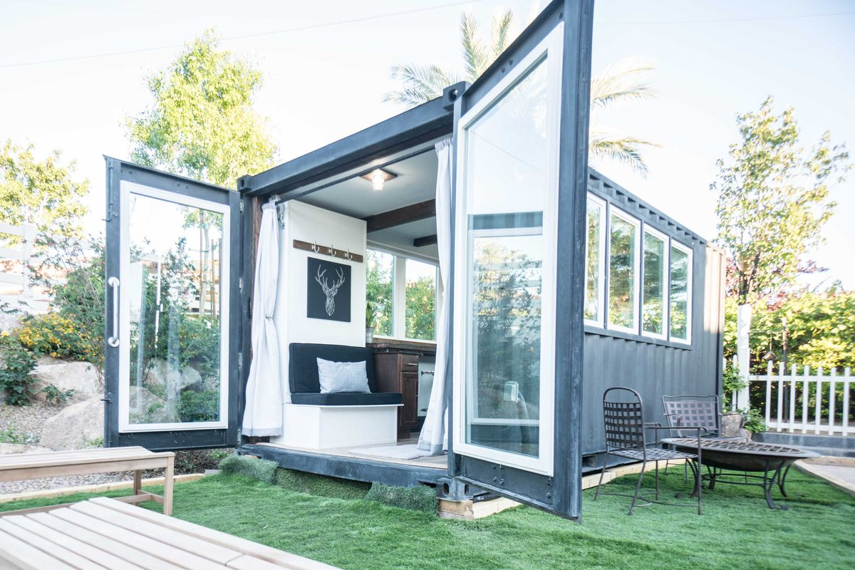 A black shipping container house has rear doors open so you can see inside.