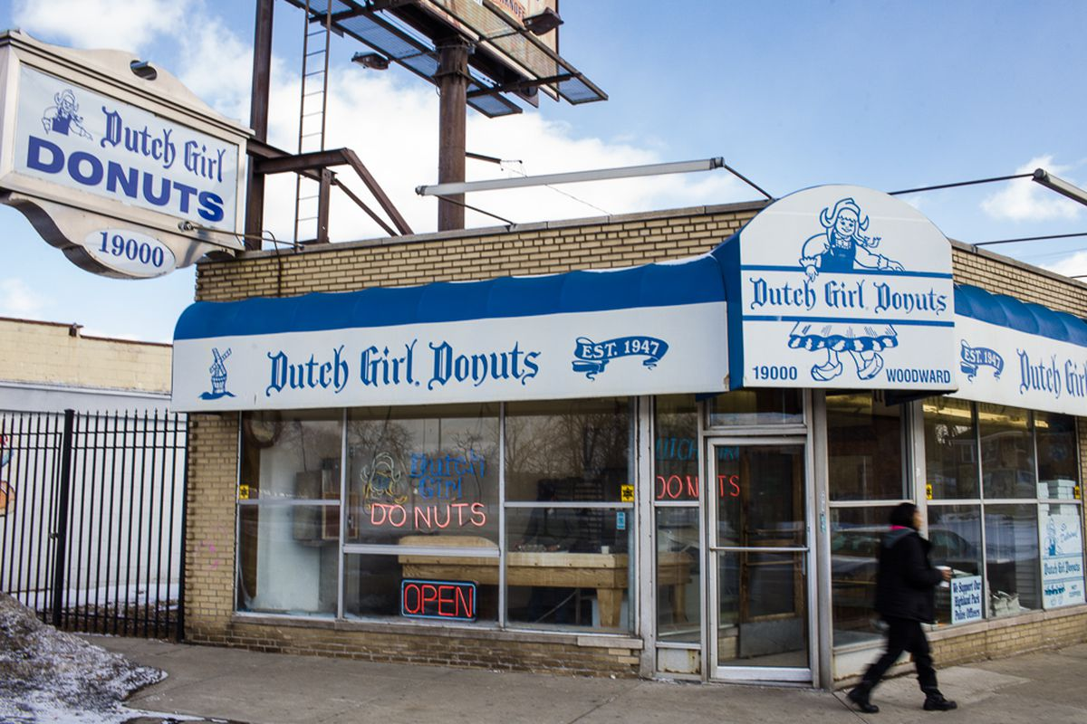 The exterior of Dutch Girl Donuts, which is on the corner of two streets. OPEN and DONUTS signs appear in the window