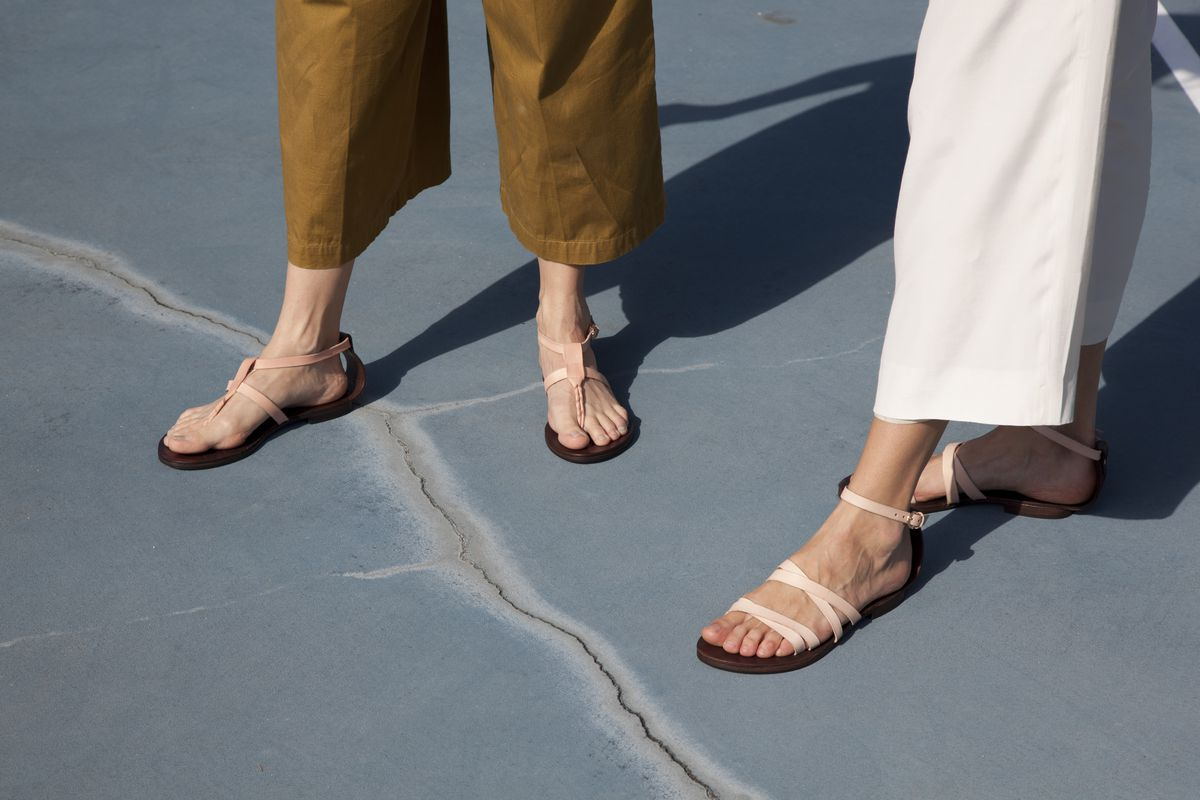 A close up of two women wearing pale pink sandals that criss-cross over the foot.