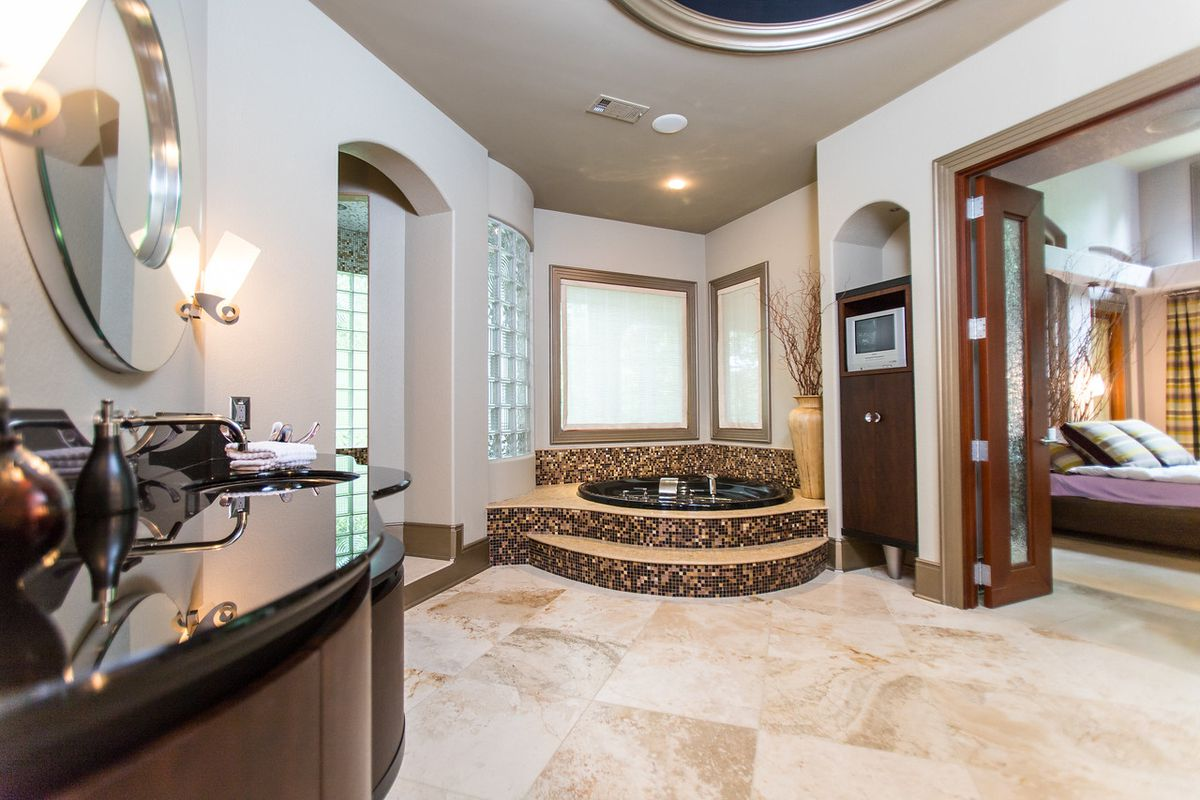 A huge master bathroom with a hot tub and vanity at left.