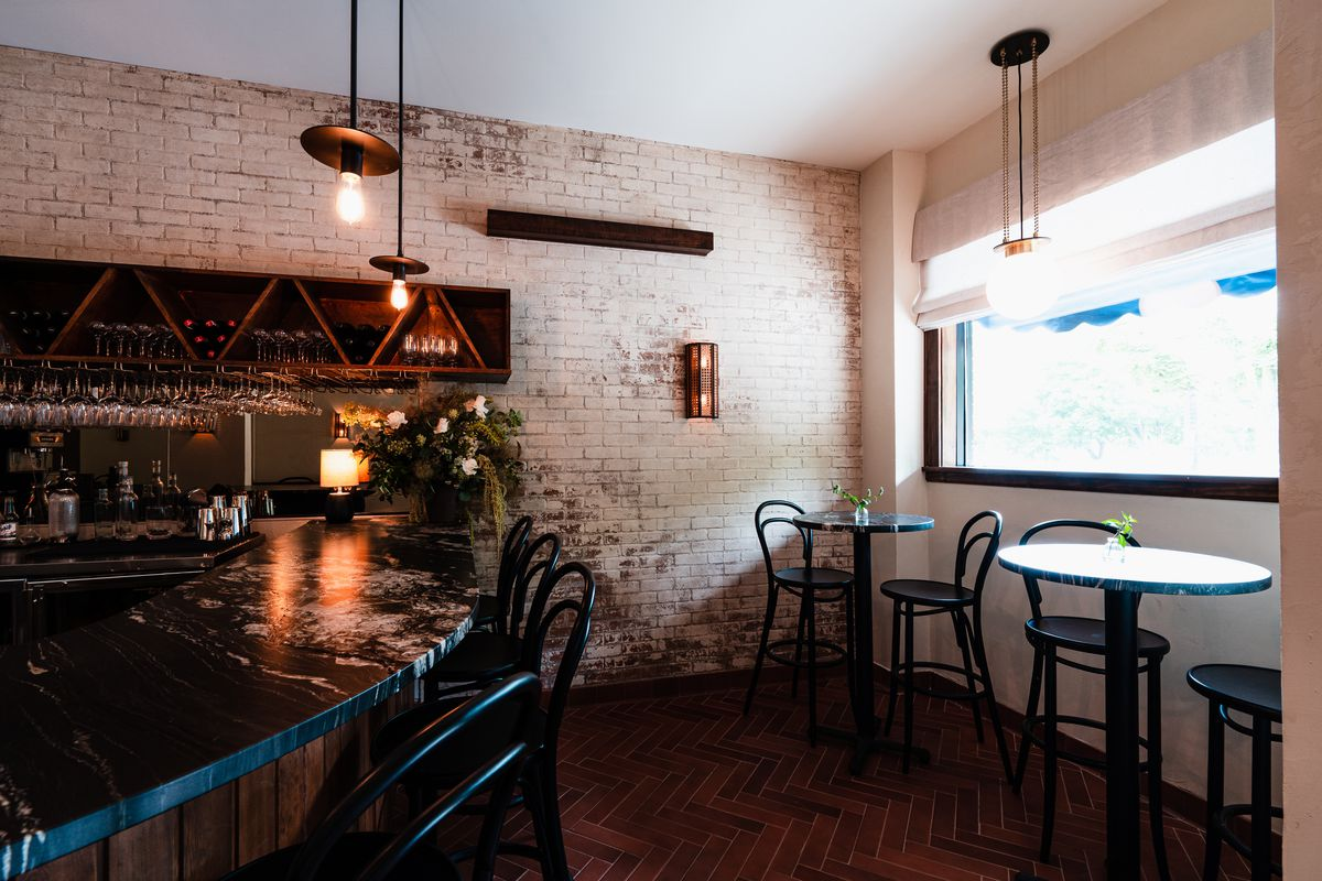The bar space in Myriel is small, lined by brick walls with two tall two-top tables by the front window, and a curved stone bar lined by tall, black bar seats. All the fixtures behind the bar are a dark wood, giving the whole space a rustic European feel.